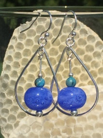 E6 $25 These blue glass beads are accented with a turquoise gemstone bead and sterling silver. These hang 1 and 1/2 inches.